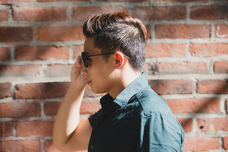 Young Asian American man adjusting sunglasses by Lauren Naefe for Stocksy United