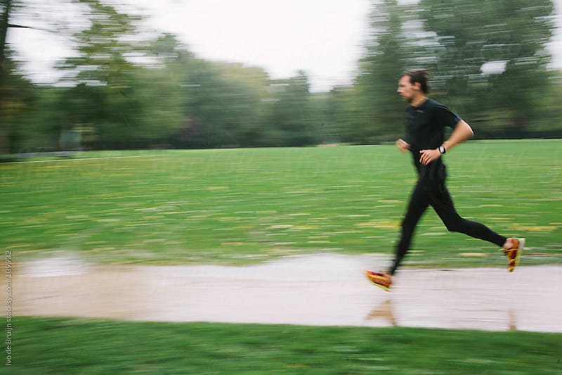 Blurry photo of a man running in the rain by Ivo de Bruijn for Stocksy United