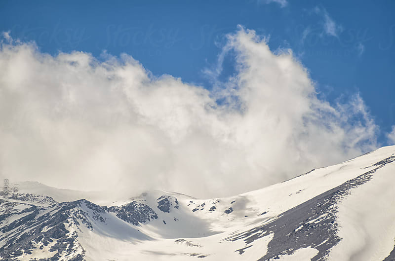 Clouds rising from snowy mountain peak by Alice Nerr for Stocksy United