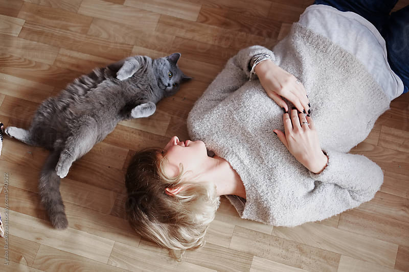 Woman lying on floor with her cute cat by Lyuba Burakova for Stocksy United