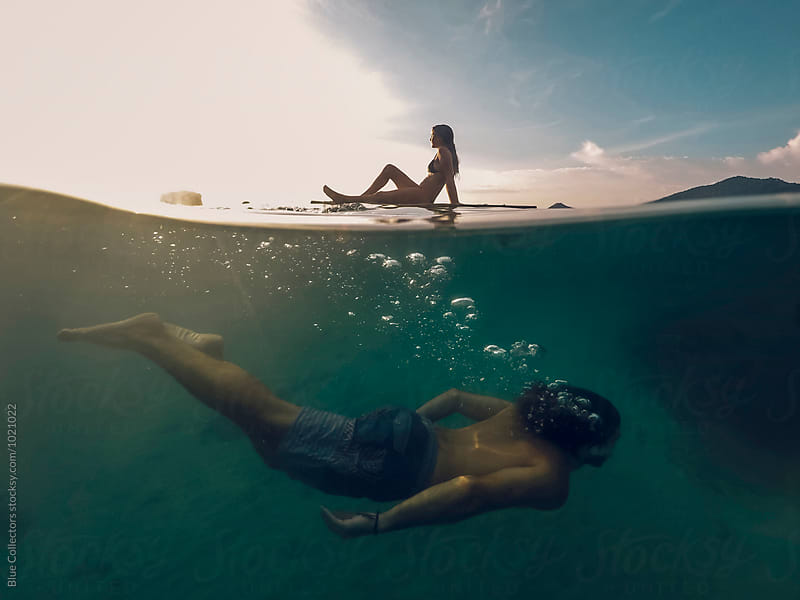 A man diving under his girlfriend enjoying the sunset on a thailand beach by Blue Collectors for Stocksy United