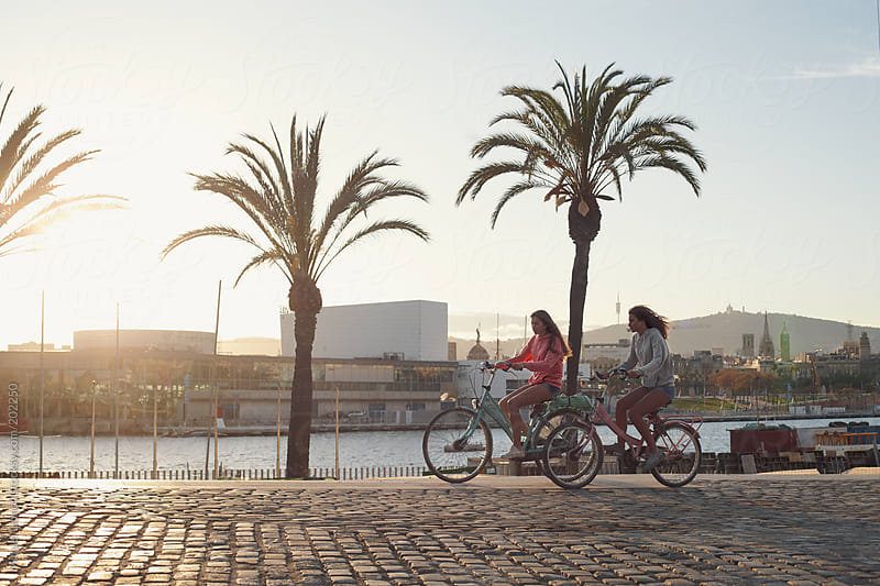 Two young girls riding a bike by the seaport of Barcelona city by Miquel Llonch for Stocksy United