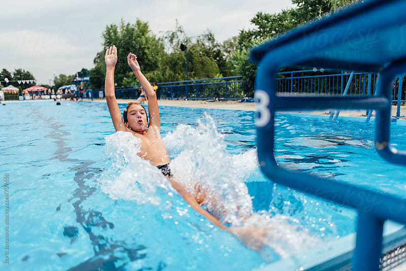 Young boy jumping backwards from swimming starting block by Boris Jovanovic for Stocksy United