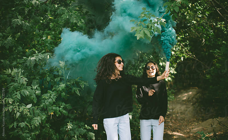 beautiful twins playing with green smoke bomb . by Alexey Kuzma for Stocksy United