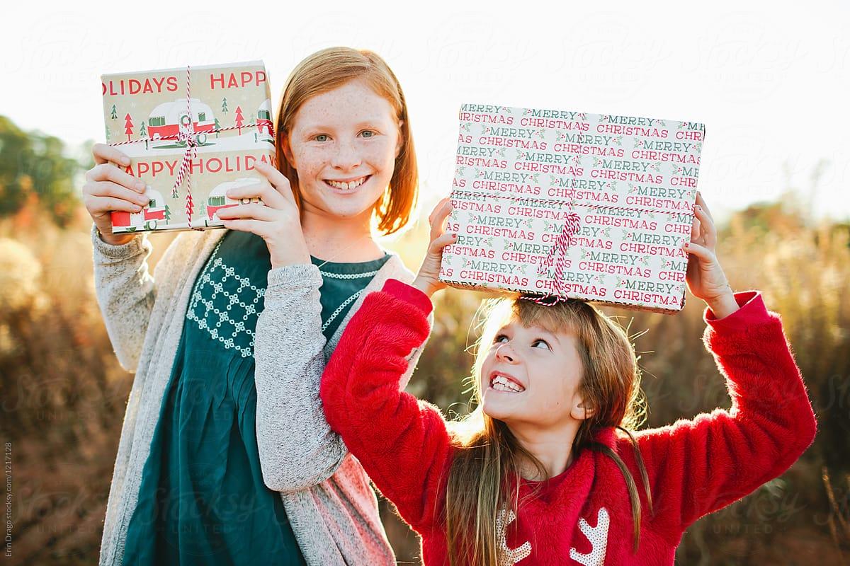 2 Little Girls Holding Christmas Gifts | Stocksy United