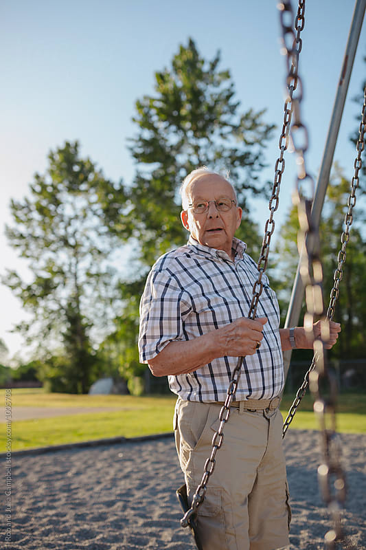 Old senior man on playground swings by Rob and Julia Campbell for Stocksy United