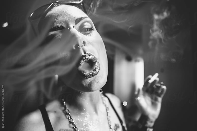 smoke,fashionable tattooed girl on the street,black and white by Igor Madjinca for Stocksy United