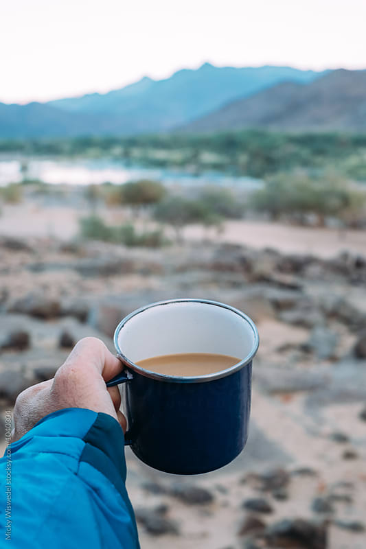 Point of view of a man holding a camping mug with coffee in a desert wilderness at dawn by Micky Wiswedel for Stocksy United