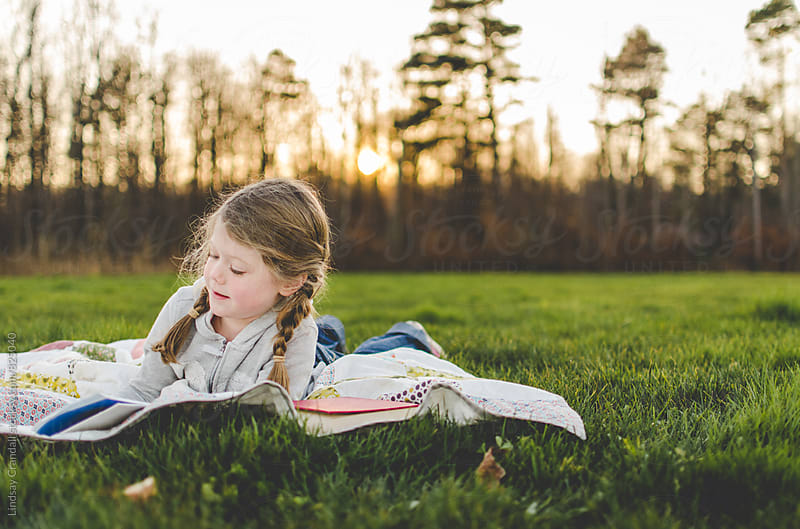 Girl reading in a field by Lindsay Crandall for Stocksy United