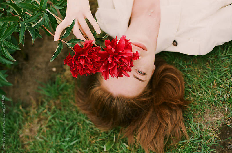 Young woman looking through red peony by Liubov Burakova for Stocksy United