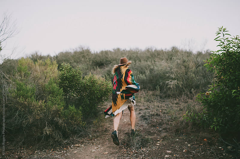 Stylish woman running with blanket at dusk in field by Kristin Rogers Photography for Stocksy United