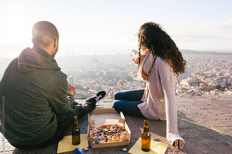 Back view of a couple eating pizza above Barcelona. by BONNINSTUDIO for Stocksy United