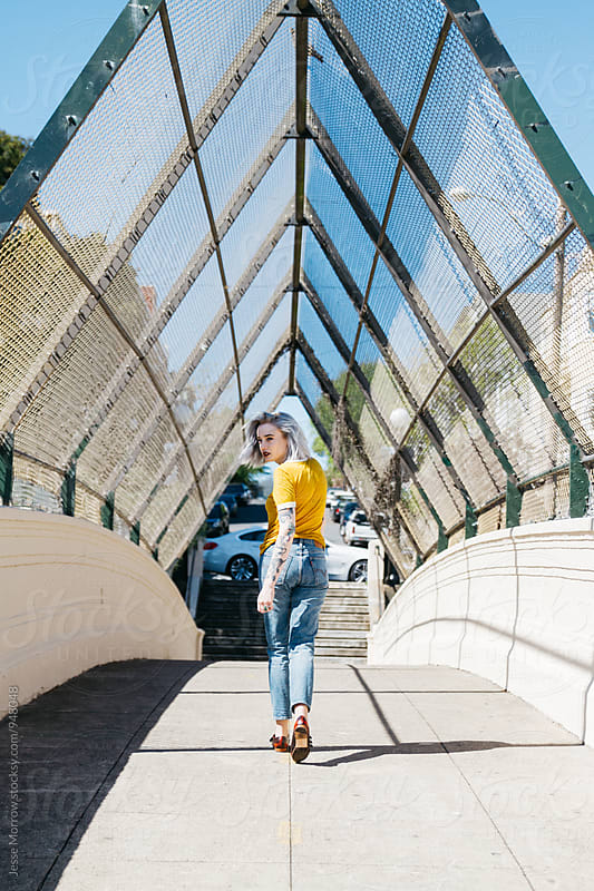 young woman model walking in alley way bridge with chain link fence  by Jesse Morrow for Stocksy United