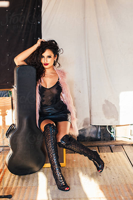 Rock n Roll woman in black leather posing with guitar by Kristen Curette Hines for Stocksy United