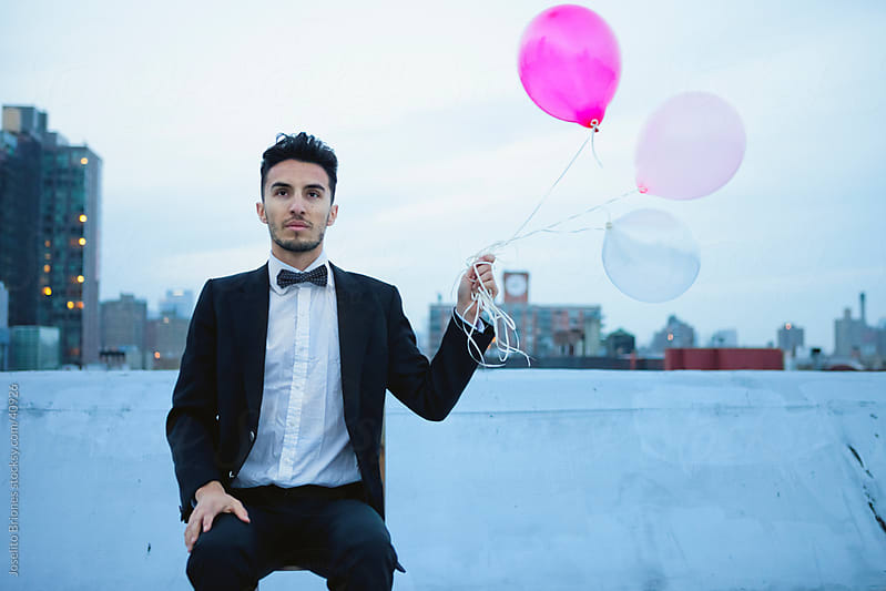 Young Man in a Suit with Balloons on Rooftop in New York by Joselito Briones for Stocksy United