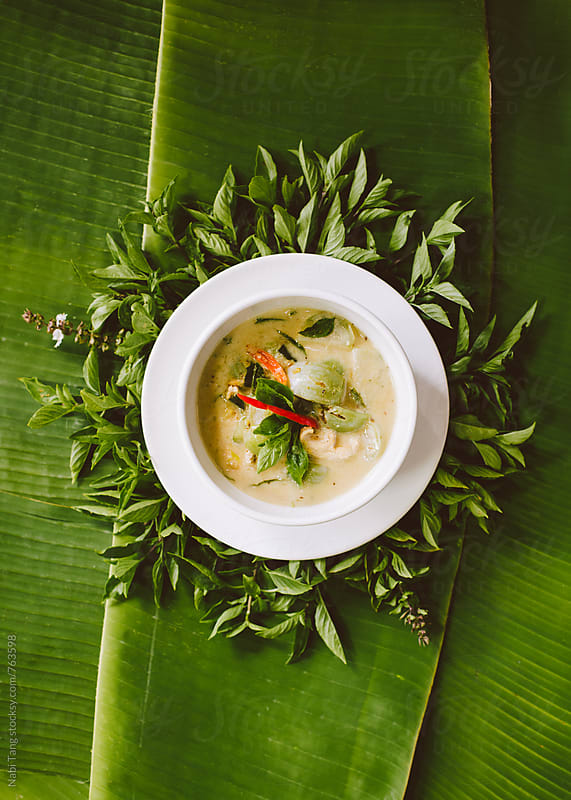 Thai chicken green curry soup styling on banana leaves by Nabi Tang for Stocksy United