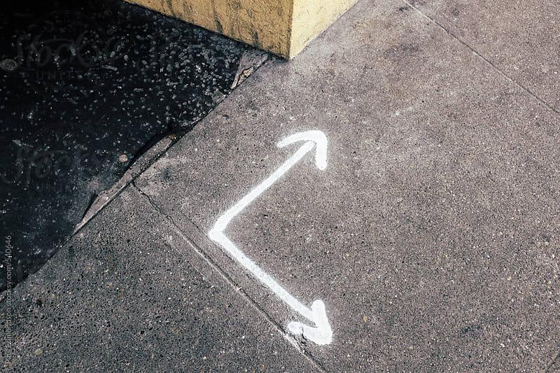 White arrows spray painted on urban sidewalk, corner of building wall in background by Paul Edmondson for Stocksy United