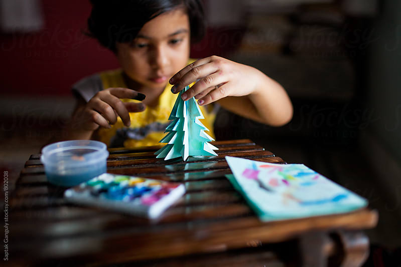 Little girl coloring a paper christmas tree by Saptak Ganguly for Stocksy United