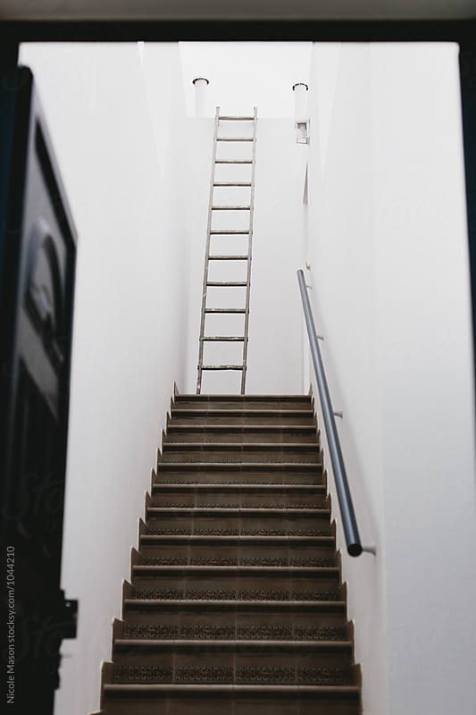 ladder at the end of stairway in white wall home by Nicole Mason for Stocksy United