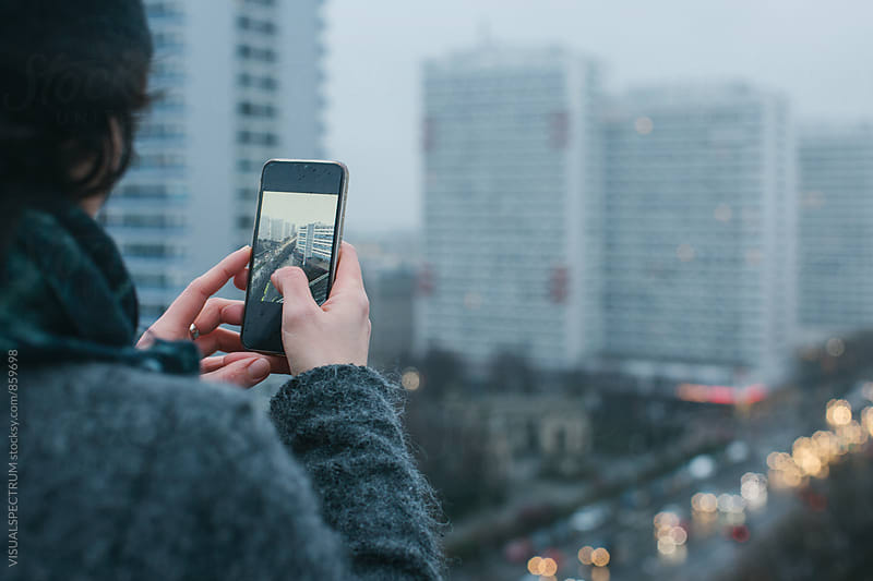 Woman Taking Photo with Cellphone on Berlin Rooftop on Rainy Winter Day by Julien L. Balmer for Stocksy United