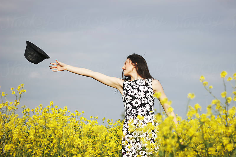 Young woman throwing her hat in the field by Jovana Rikalo for Stocksy United