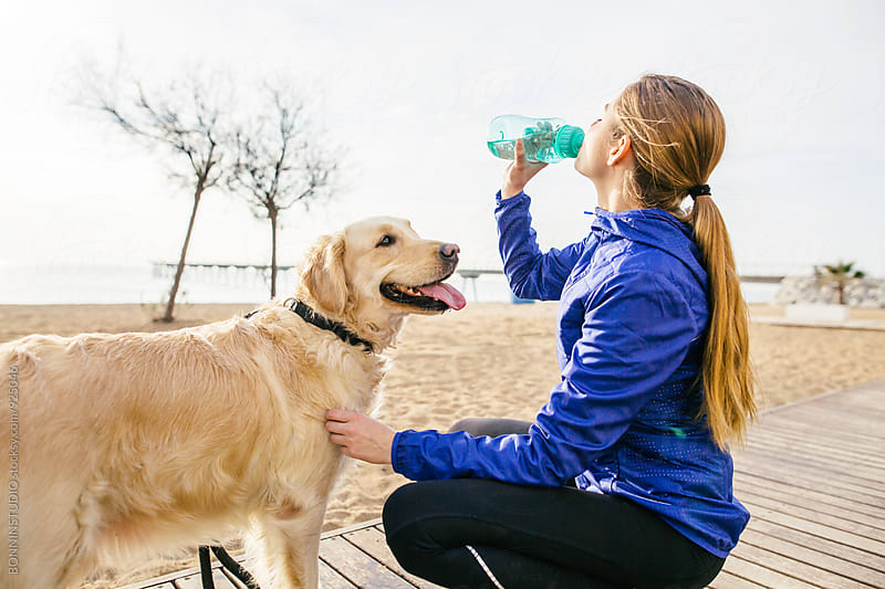 Runner woman with her dog drinking water after workout.   by BONNINSTUDIO for Stocksy United