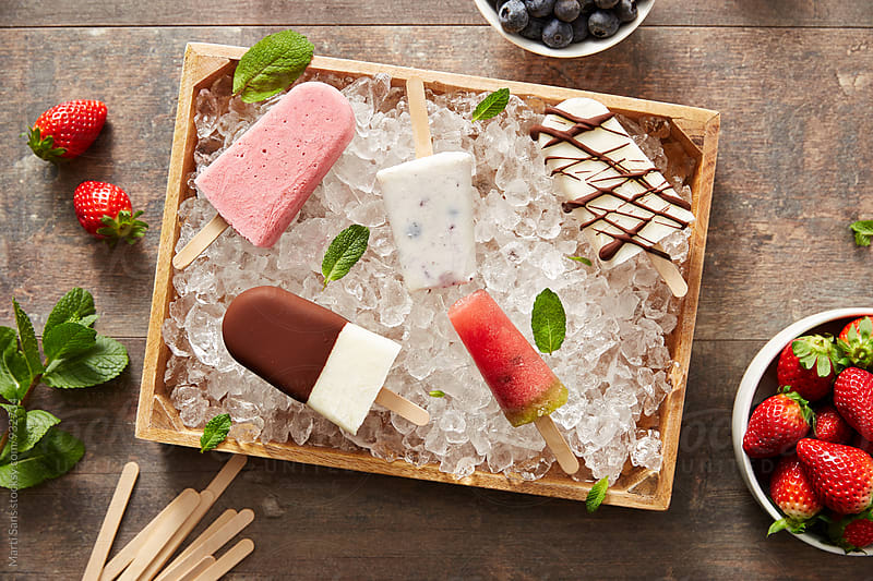 Amazing popsicles in ice basket from above by Martí Sans for Stocksy United