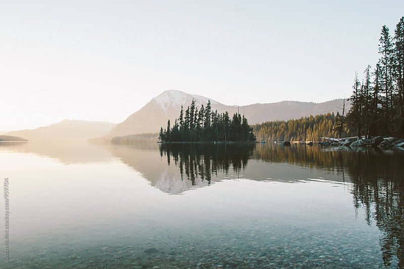 Beautiful mountain scenery and a small island on a calm lake at sunset by Justin Mullet for Stocksy United