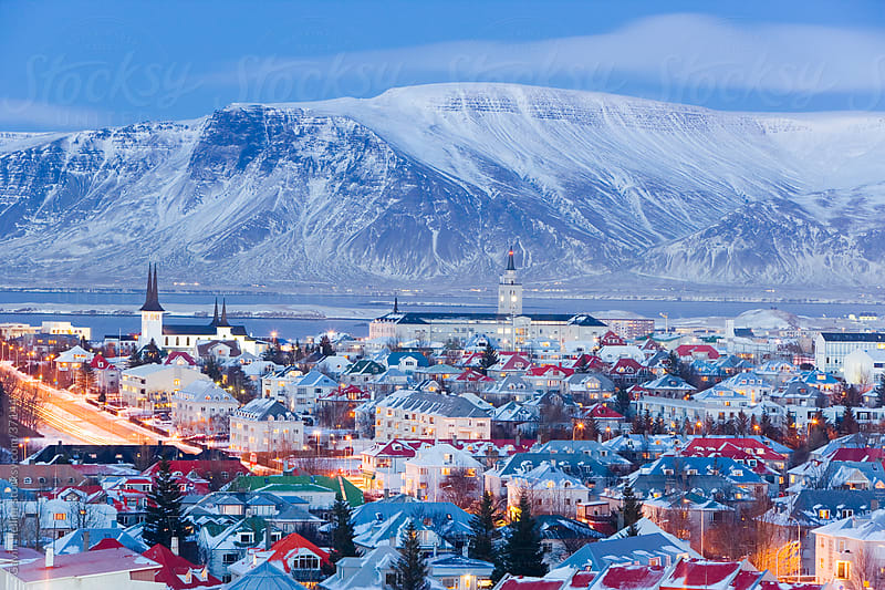 Iceland, Reykjavik, elevated view over the Churches and cityscape of Reykjavik with a backdrop of snow capped mountains by Gavin Hellier for Stocksy United