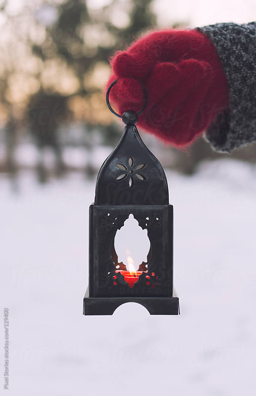 Hand holding Christmas lantern by Pixel Stories for Stocksy United