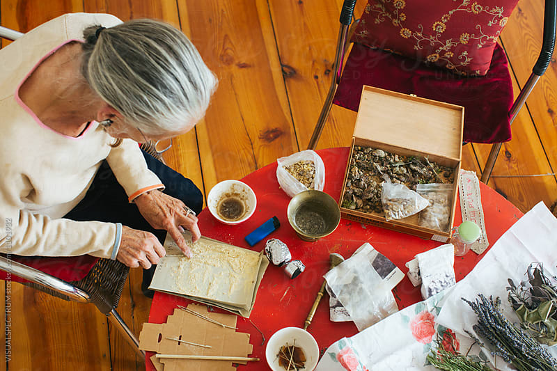 Overhead Shot of Senior Woman with Grey Hair Making Natural Incense by Julien L. Balmer for Stocksy United
