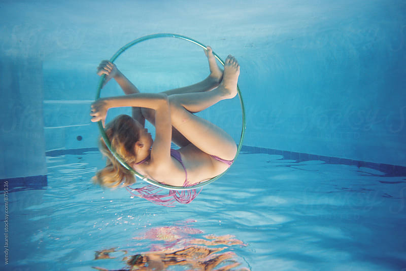 girl in hula hoop underwater in blue pool on film by wendy laurel for Stocksy United