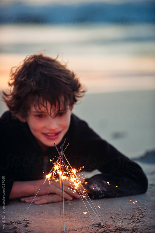 Boy playing with firework sparklers at the beach at sundown by Angela Lumsden for Stocksy United