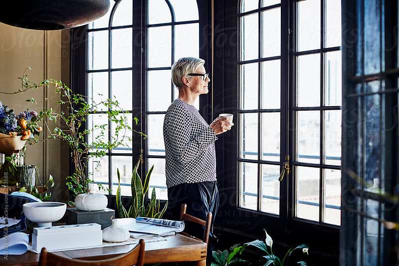 Senior Woman Having Coffee While Looking Through Window by ALTO IMAGES for Stocksy United