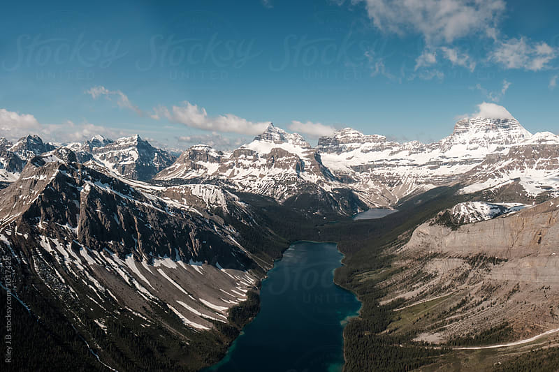 A glacial lake between mountains of the Canadian Rockies by Riley Joseph for Stocksy United