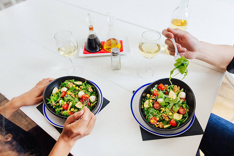 Couple eating a healthy salad from above in a restaurant.