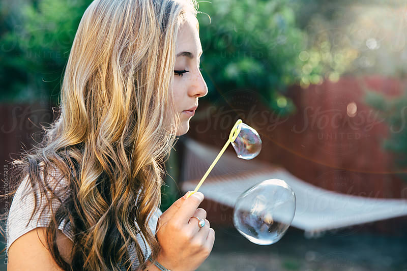 Profile of a teenage girl with long, wavy hair blowing bubbles by Carolyn Lagattuta for Stocksy United
