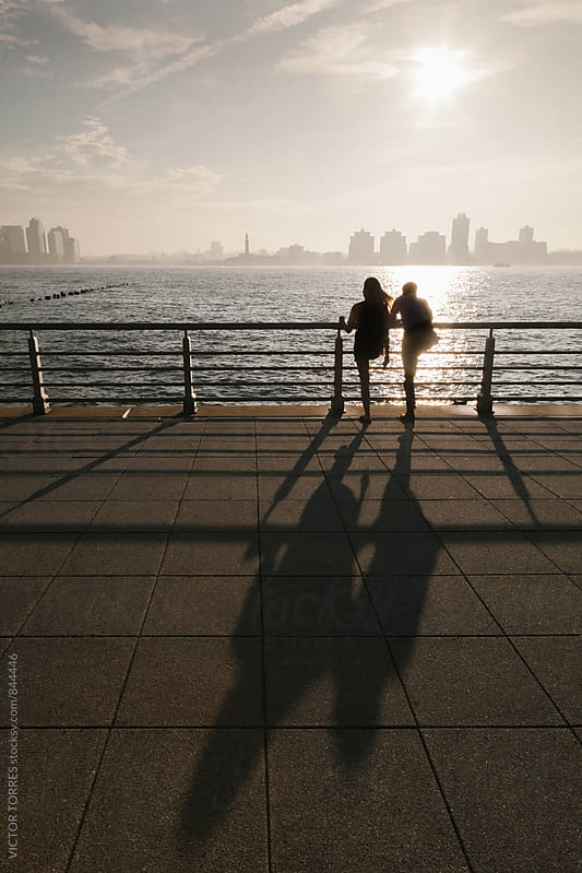 Couple Admiring the Sunset in the Hudson River with Jersey City Skyline at the Background by VICTOR TORRES for Stocksy United