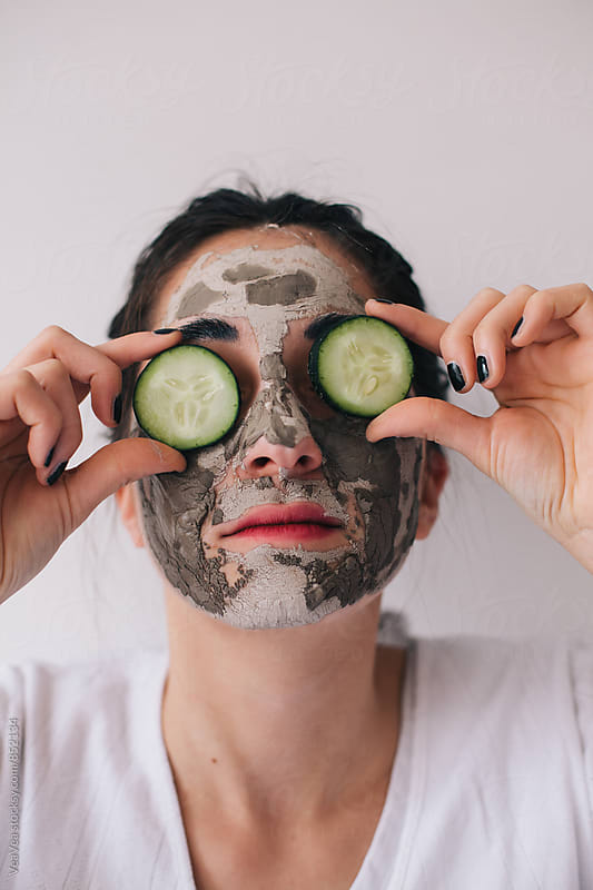 Portrait of a brunette woman with facial mask and slices of cucumbers on her eyes by Marija Mandic for Stocksy United