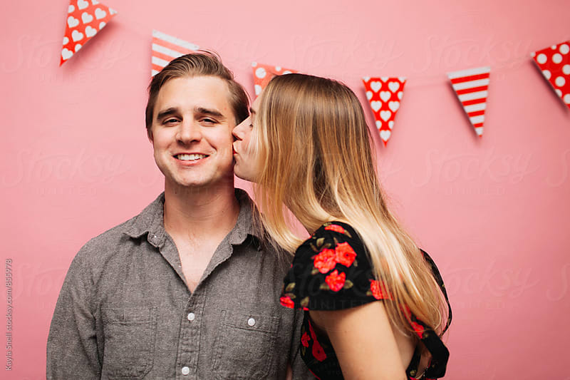 A woman kissing her boyfriend on the cheek by Kayla Snell for Stocksy United