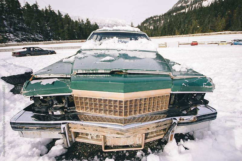 Old vintage racing car abandoned on snow junk field by Alejandro Moreno de Carlos for Stocksy United