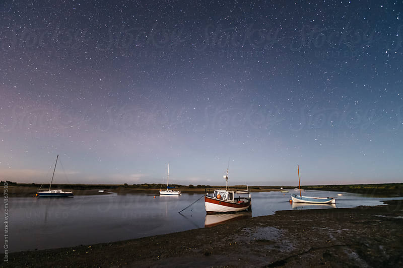 Boats under stars on a moonlit night. Burnham Overy Staithe, Norfolk, UK. by Liam Grant for Stocksy United