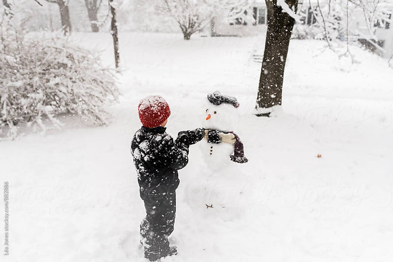 Little boy making a snowman in front of his house.   by Léa Jones for Stocksy United