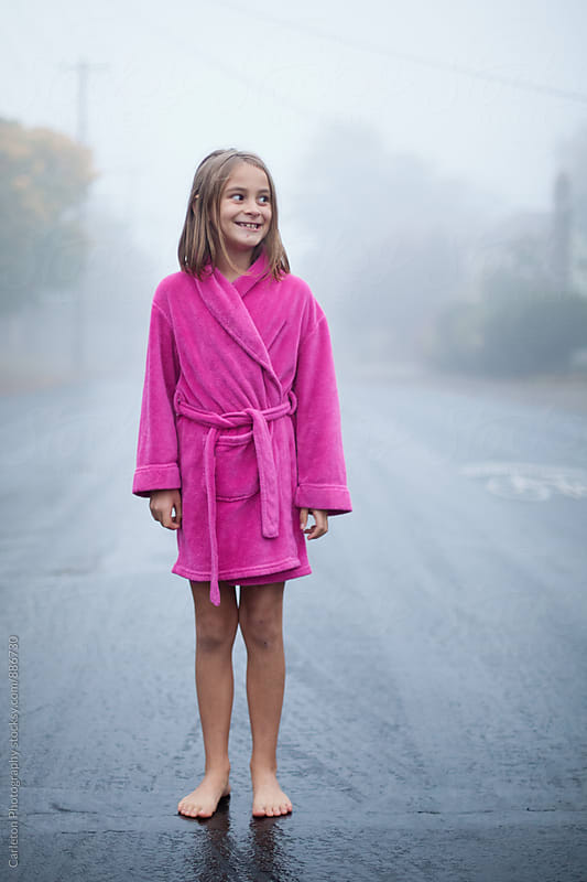 Barefoot girl in pink bathrobe stands on a wet street on a foggy morning in Portland, Oregon by Carleton Photography for Stocksy United