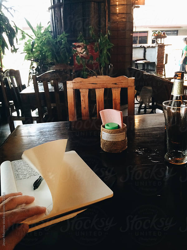 Young man writes in journal diary on vacation by Jesse Morrow for Stocksy United