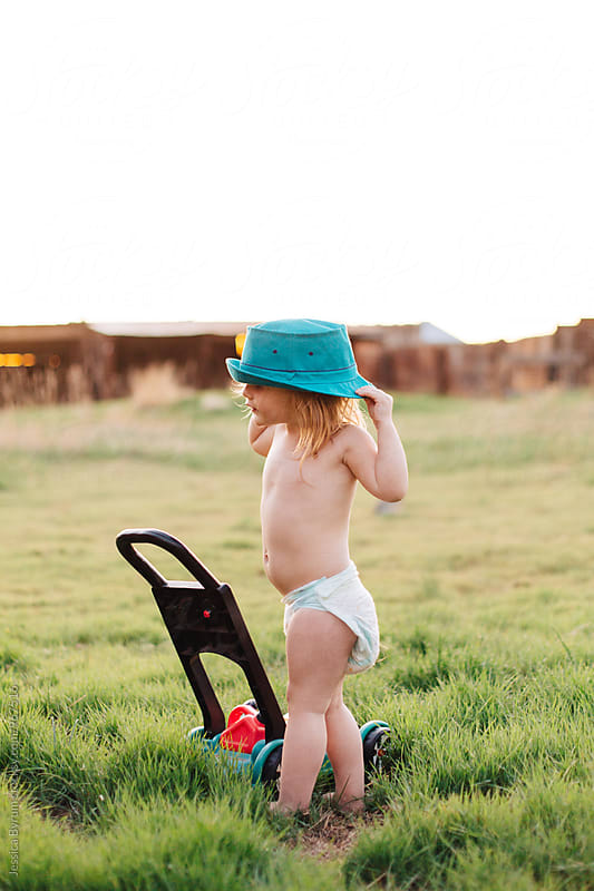 Toddler girl pulling hat down by Jessica Byrum for Stocksy United