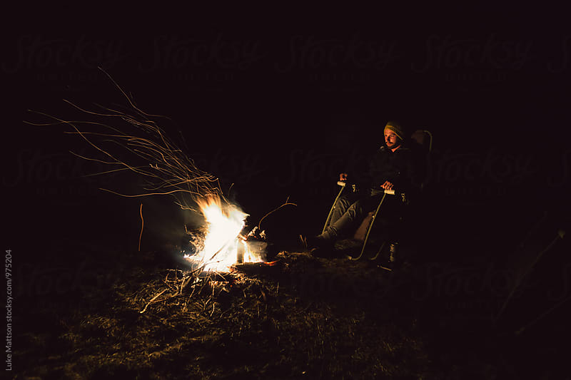 Young Man Sitting In Chair By Campfire At Night by Luke Mattson for Stocksy United