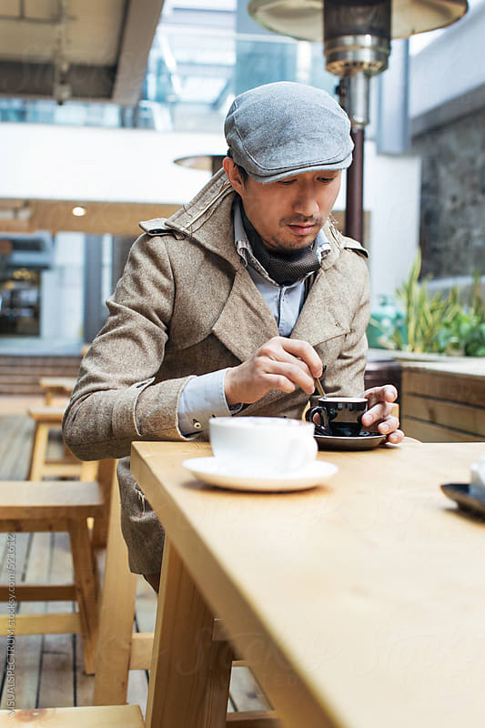 Good-Looking Young Asian Man Having Espresso in Bright Café by VISUALSPECTRUM for Stocksy United