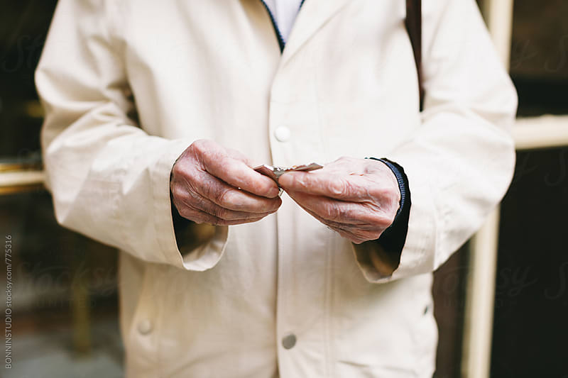Anonymous elderly man holding a key on the street. by BONNINSTUDIO for Stocksy United