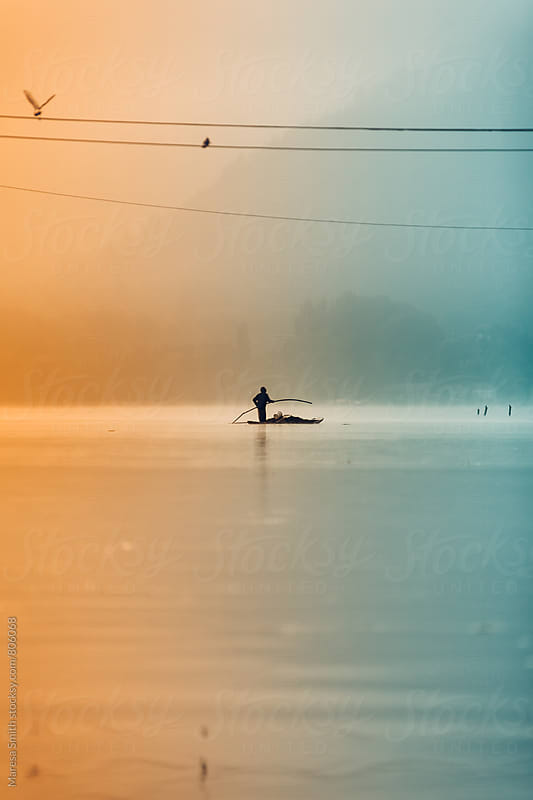 A silhouetted man makes his way across Dal Lake at sunrise by Maresa Smith for Stocksy United
